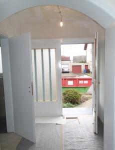 Blick von der Diele nach draußen, die Türen sind grundiert, die Wände bereits gespachtelt, der polierte Werksteinboden ist bereits abgedeckt.