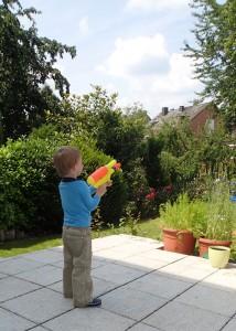 Mit der Wasserpistole im Garten